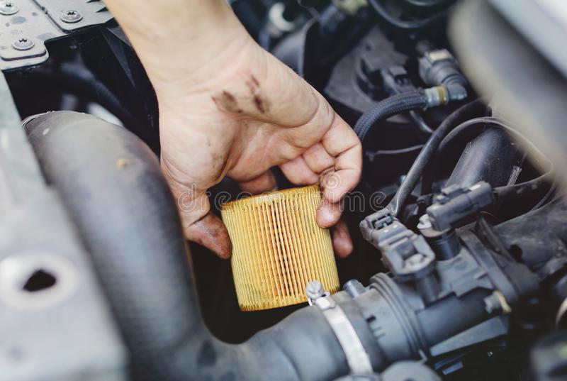 Close up hand of mechanic doing car service and maintenance - Oil and fuel filter changing royalty free stock images
