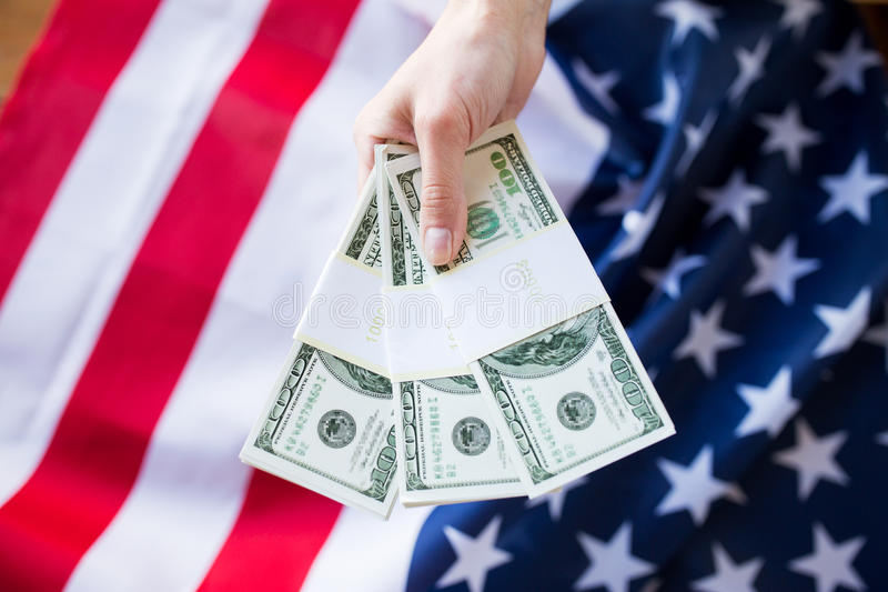 Close up of hand with money over american flag. Finances, corruption, investment and economics concept - close up of hand with dollar cash money over american royalty free stock images