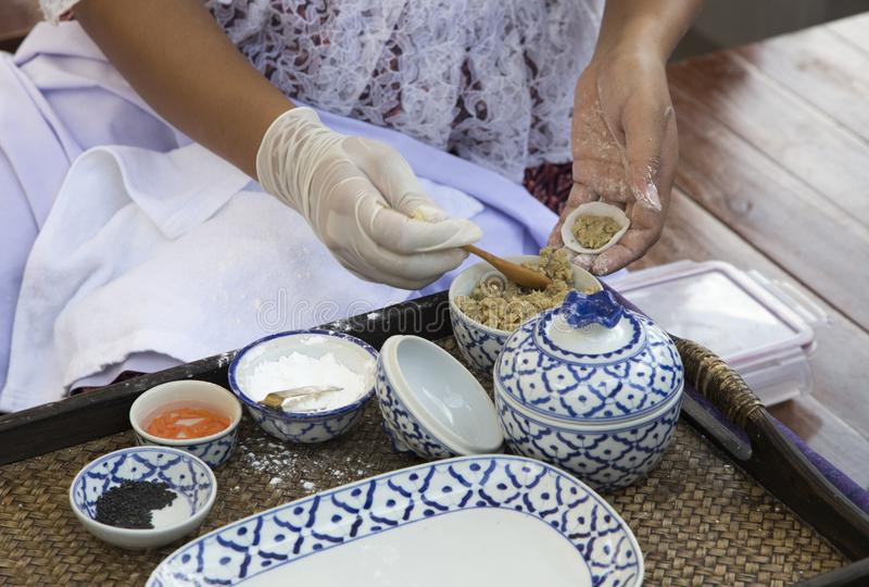Close up hand of old woman make Thai dessert food with ceramic b stock image