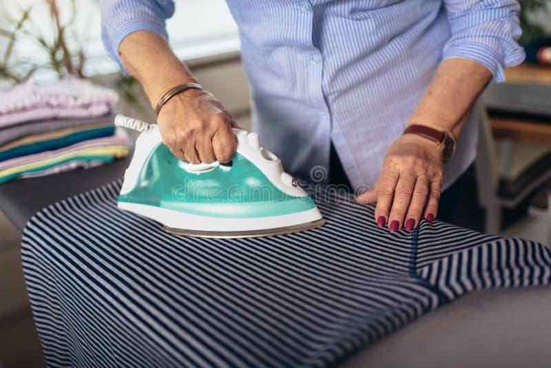 Close up hand older woman ironing royalty free stock photo