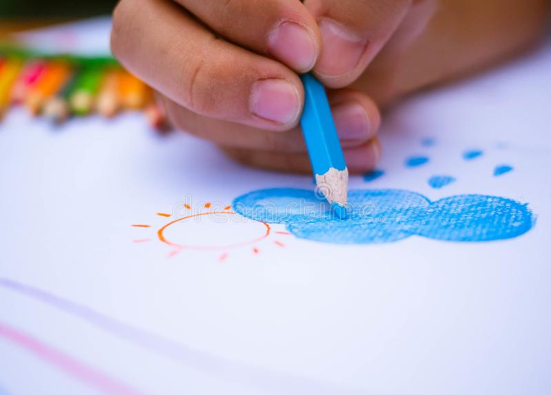 Close up hand of painting Clouds, rain and sun on white paper background. Education concept stock images