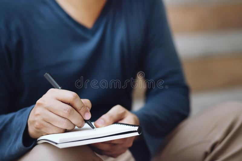 Close up hand people man are sitting on a staircase. using pen writing Record Lecture note pad into the book in park public. stock image