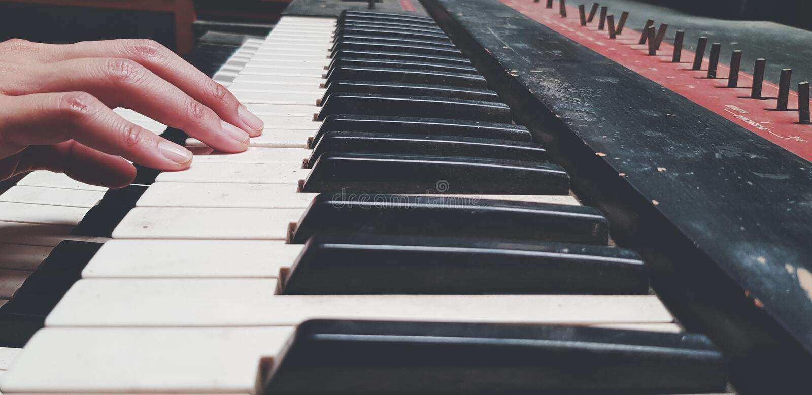 Close up hand of people playing piano or press elect tone keyboard in vintage color style. Object, Music and Instrument concept stock images