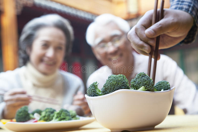 Close up of hand picking up broccoli with chopsticks stock photography