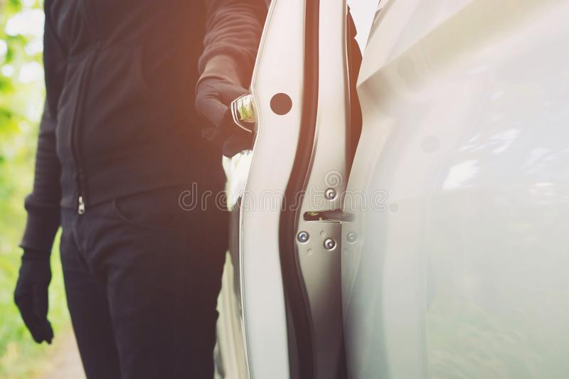 Close up hand pulling the handle of a car thief  wearing black clothes and glove stealing automobile trying door handle to see if stock photography