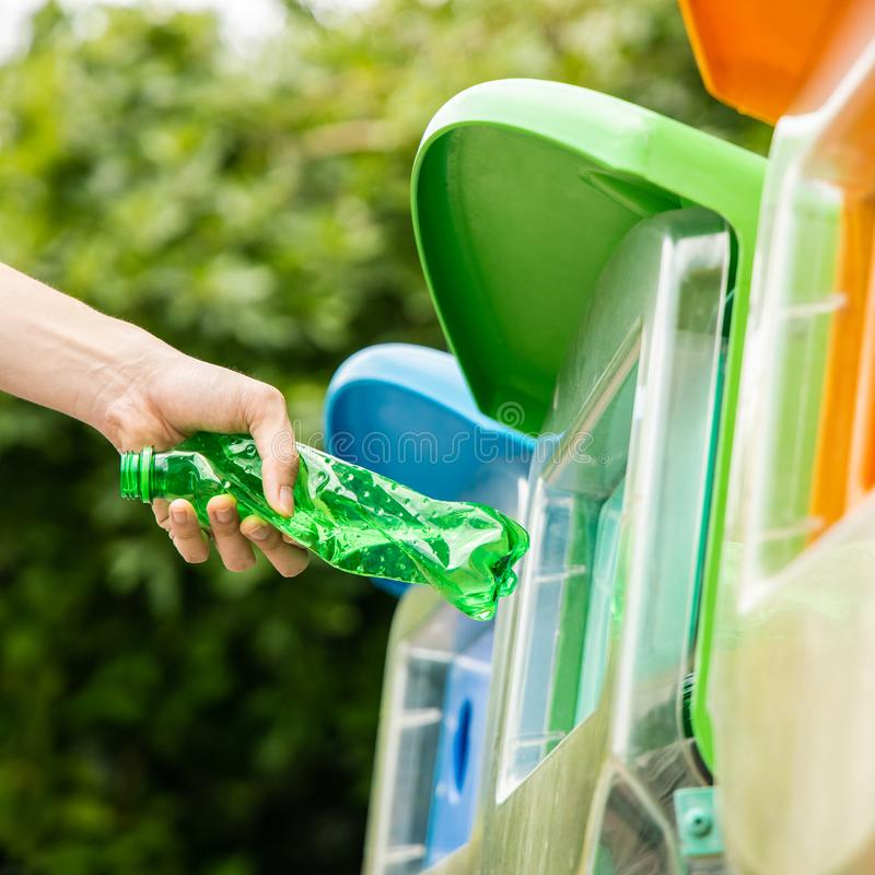 Close up hand put plastic bottle into bin. Close up shot, hand putting twisted green empty plastic bottle into recycle bin in public stock photography