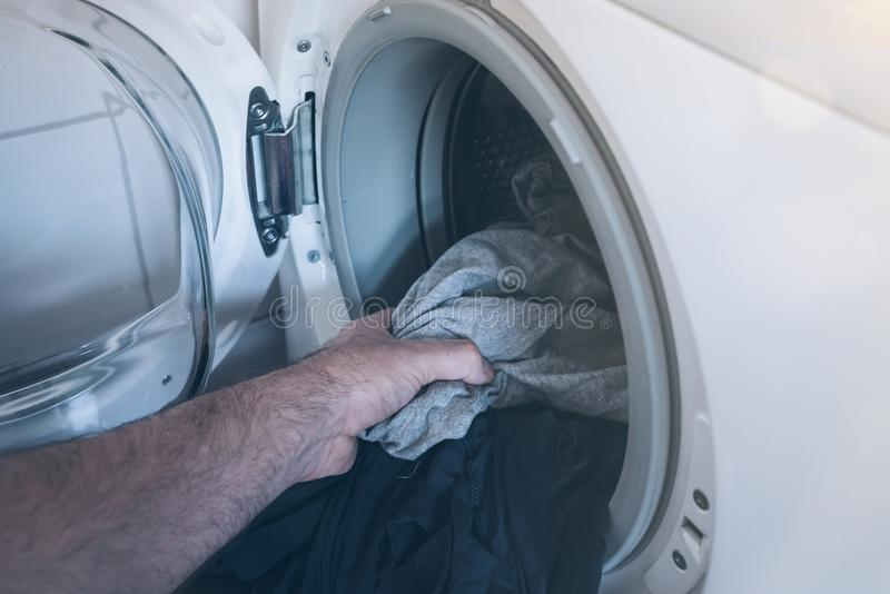 Close-up of hand putting dirty laundry in drum of washing machine. Close-up of male hand putting dirty laundry in drum of washing machine stock photo