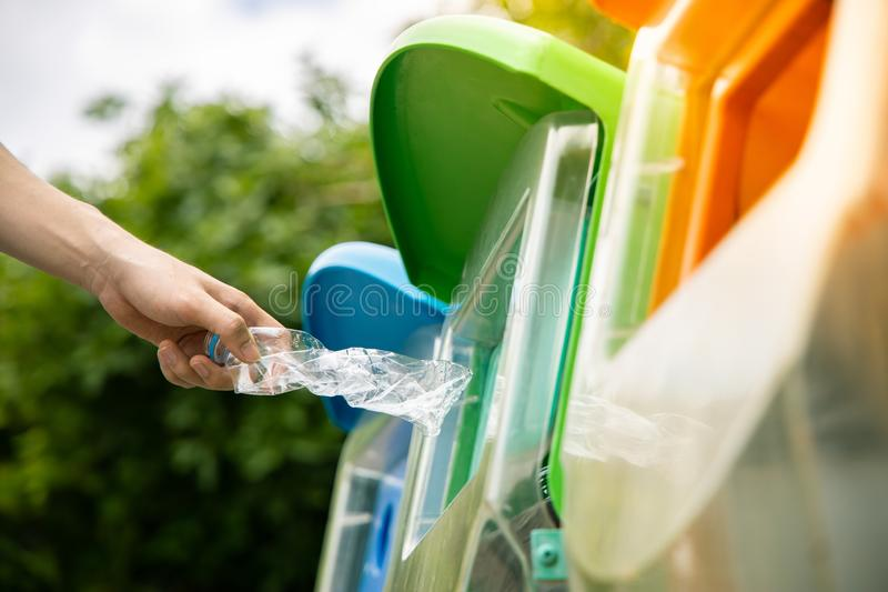 Close up hand putting plastic bottle into bin. Close up shot, hand putting twisted empty plastic drinking water bottle into recycle bin in public royalty free stock images