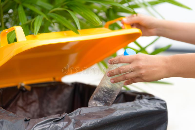 Close up Hand putting plastic bottle waste into garbage trash stock photography