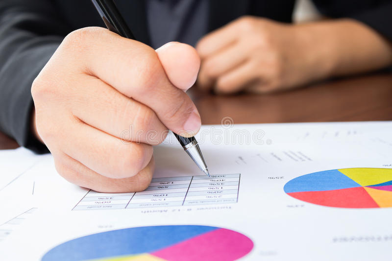 Close up of hand reviewing accounting documents royalty free stock photo