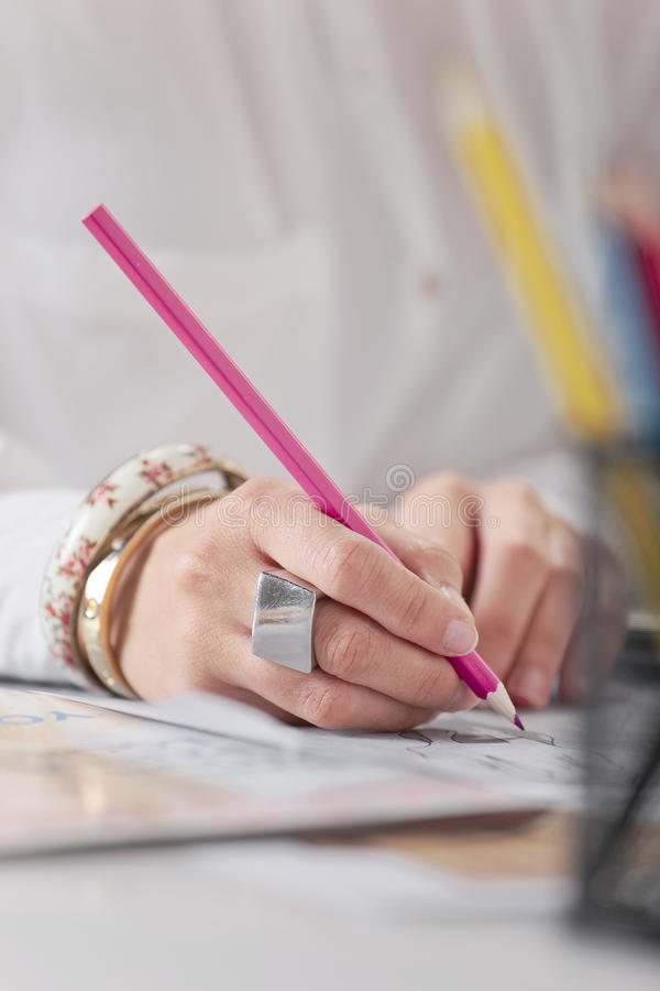 Close up of a hand's woman doing fashion sketches. Hands drawing with pink pencil royalty free stock photos