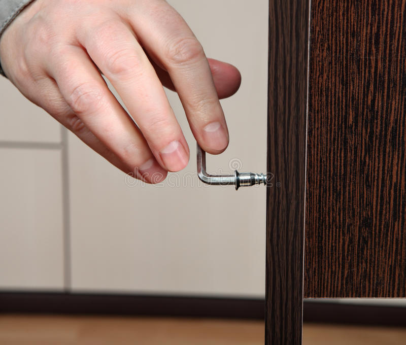 Close-up of a hand screwed hex wrench, assembling furnitur stock photography