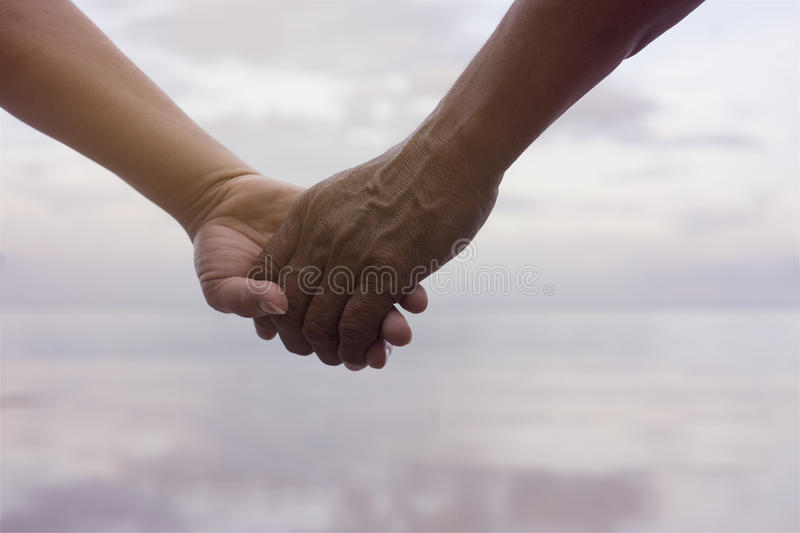 Close up hand of senior couple holding hand together near seaside at the beach,filtered image,light effect added,selective focus. Love forever concept royalty free stock images