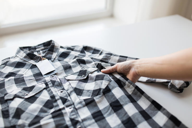 Close up of hand and shirt with price tag. Clothes, fashion, people and shopping concept - close up of hand holding checkered shirt with price tag stock photo