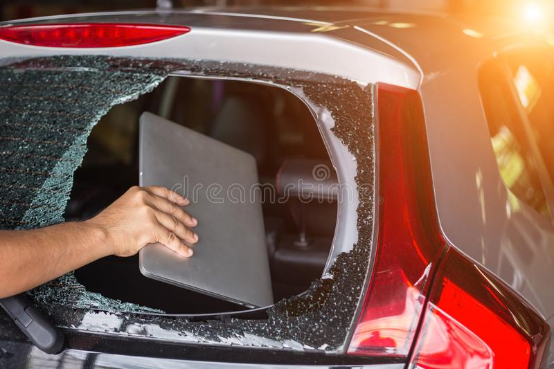Hand stealing laptop from back side of car which rear glass broken stock image
