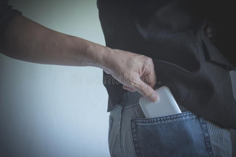 Close-up of a the hand of thief stealing the wallet to a woman. stock photo