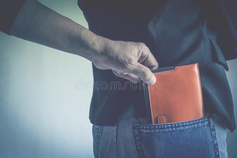 Close-up of a the hand of thief stealing the wallet to a woman. stock photography
