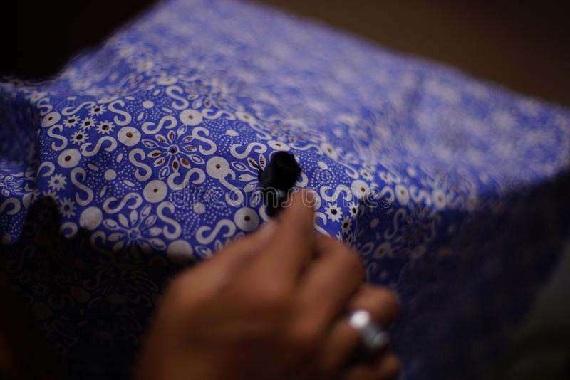 Drawing Batik Tulis on the fabric. Close Up hand to make batik with canting on the blue colour fabric stock photos