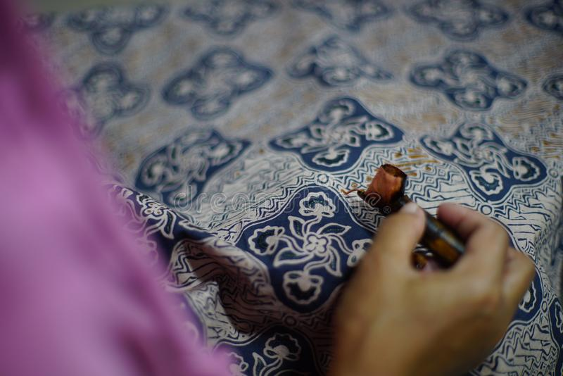 Drawing Batik Tulis on the fabric. Close Up hand to make batik with canting on fabric stock photography