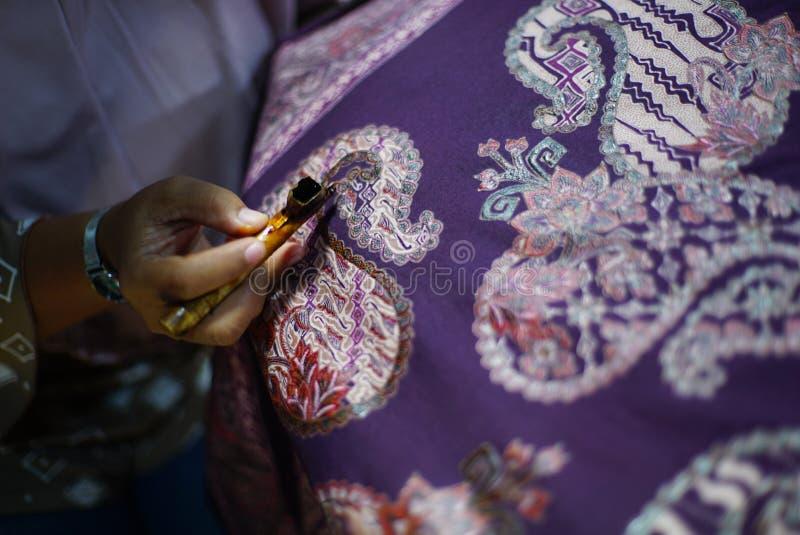 Drawing Batik Tulis on the fabric. Close Up hand to make batik with canting on fabric stock photos