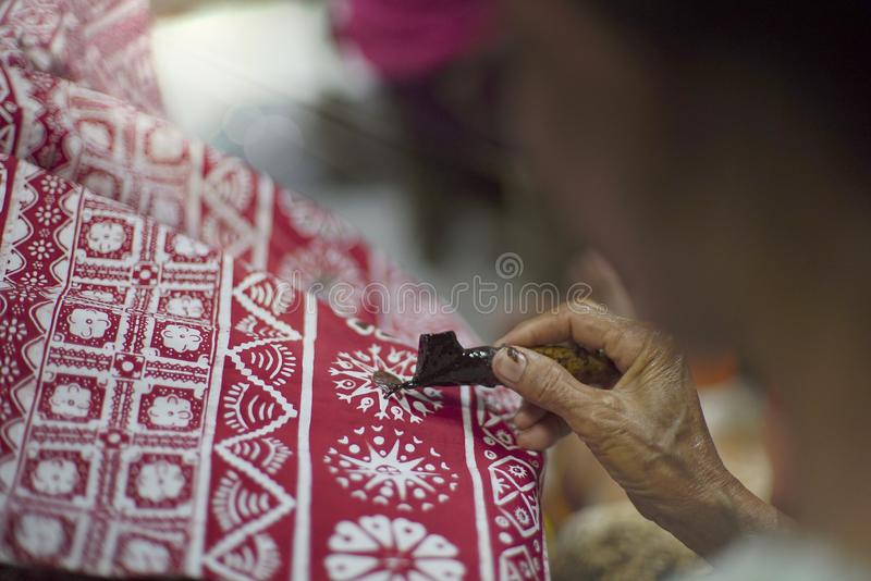 Drawing Red Batik Tulis on the fabric. Close Up hand to make batik with canting on fabric. Traditioinal Culture Indonesia royalty free stock images