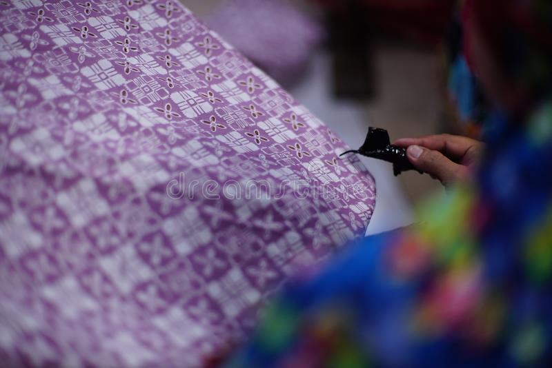 Drawing Batik Tulis on the fabric. Close Up hand to make batik with canting on the purple colour fabric stock photo