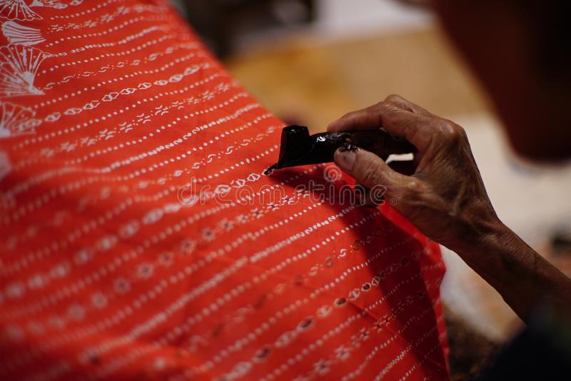 Drawing Batik Tulis on the fabric. Close Up hand to make batik with canting on the red colour fabric royalty free stock photography