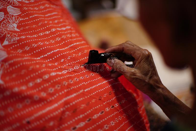 Drawing Batik Tulis on the fabric. Close Up hand to make batik with canting on the red colour fabric royalty free stock photos