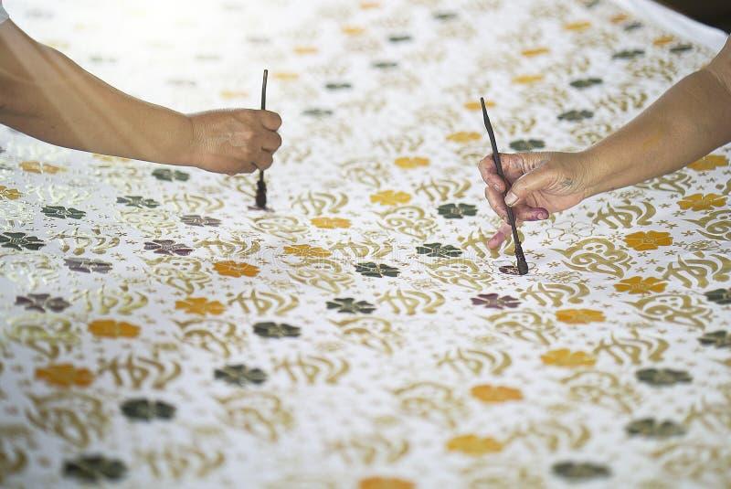 Painting Batik on the fabric stock image