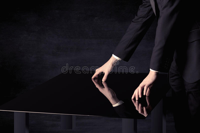 Close up of a hand touching smart table with copy space. On black background stock photos