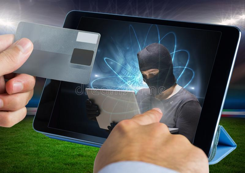 Close up of hand touching a tablet with hacker and holding credit card. Digital composite of Close up of hand touching a tablet with hacker and holding credit royalty free stock photos