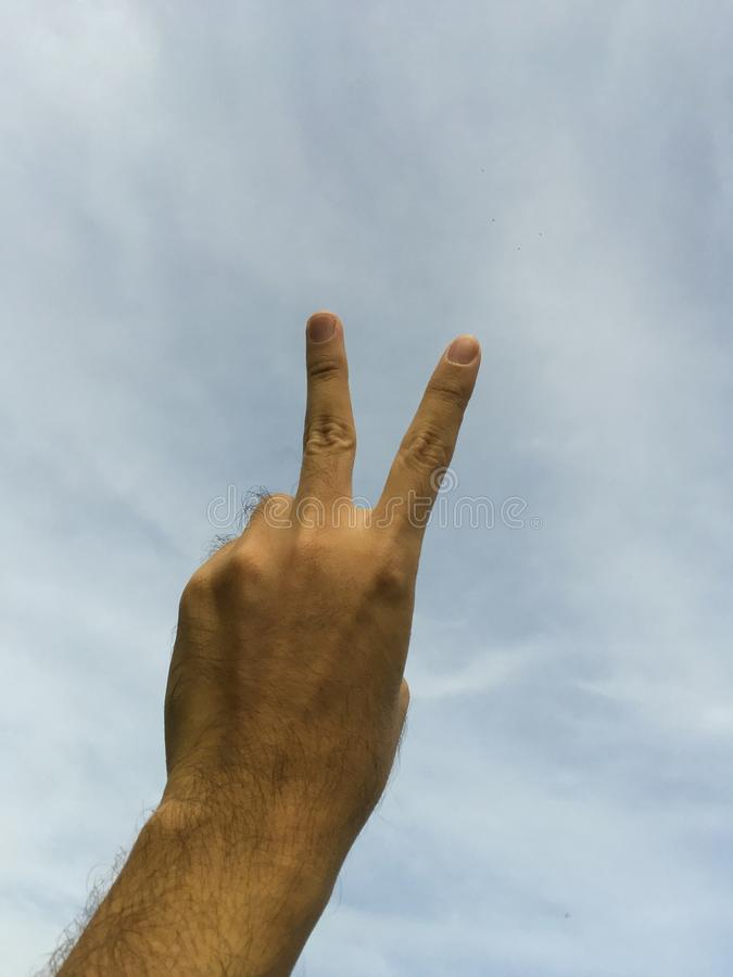 Hand with two fingers or victory sign on blue sky royalty free stock images