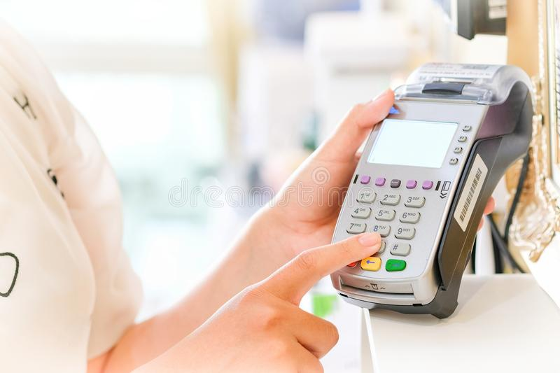 Close up of hand using credit card swiping machine to pay. Hand. With creditcard swipe through terminal for payment in cafeteria. Man entering credit card code stock images