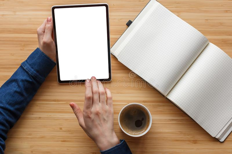 Close up hand using tablet and note book white screen on workspace table, coffee break. royalty free stock photos