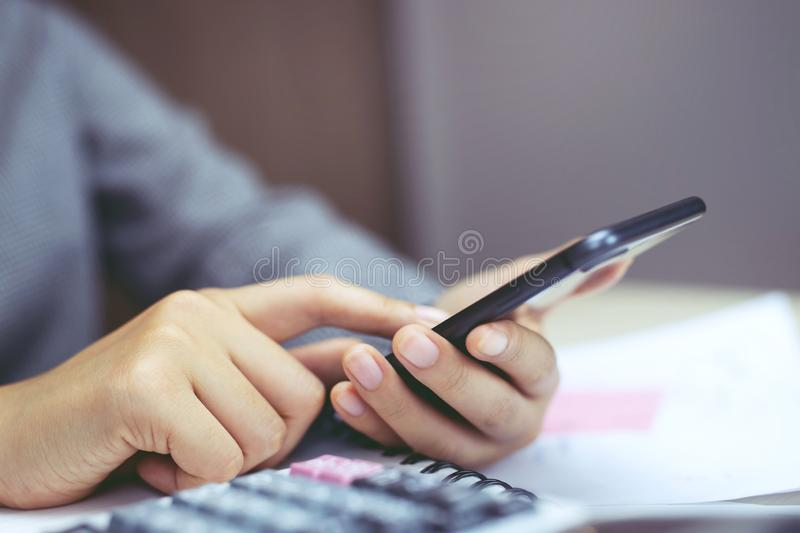 Close up hand view of business woman using calculator app on her mobile smart phone royalty free stock image