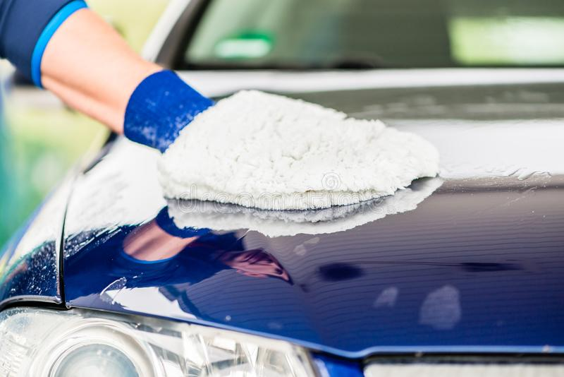 Close-up of hand wiping car with microfiber wash mitt. Close-up of male hand wiping the wet surface of a blue car with microfiber wash mitt for drying royalty free stock photography