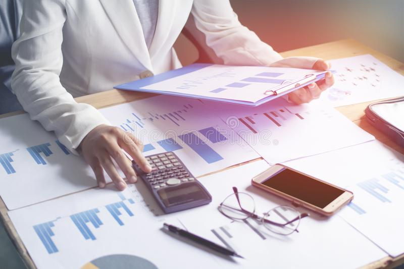 Close-up hand woman business working using a calculator and graph papers on the desk with sunset. royalty free stock image