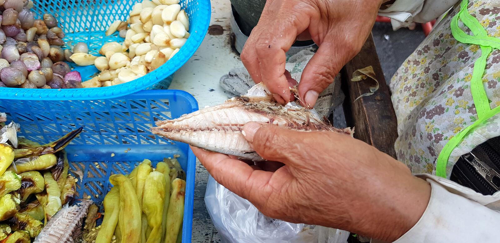Close up hand of woman or chef taking the fish bone out of mackerel with garlic grilled and green pepper at local street food. royalty free stock images