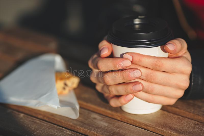 Close up of a hand of woman holding a coffee cup. And dessert on wooden table royalty free stock photo