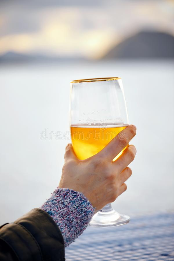 Close up hand of a woman holding a glass of beer with blurred sea, sky and island background. At sunset stock photos