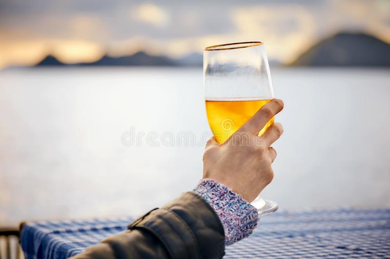 Close up hand of a woman holding a glass of beer with blurred sea, sky and island background stock photo