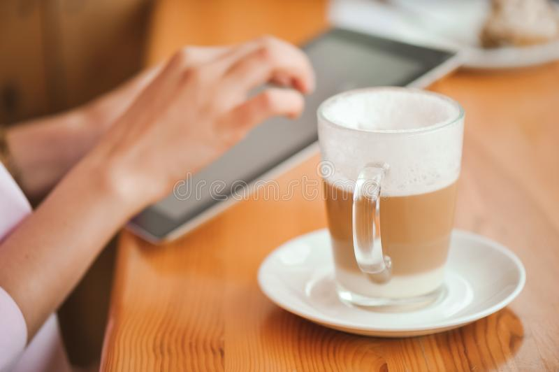 Close up hand woman using tablet in coffee shop. royalty free stock images