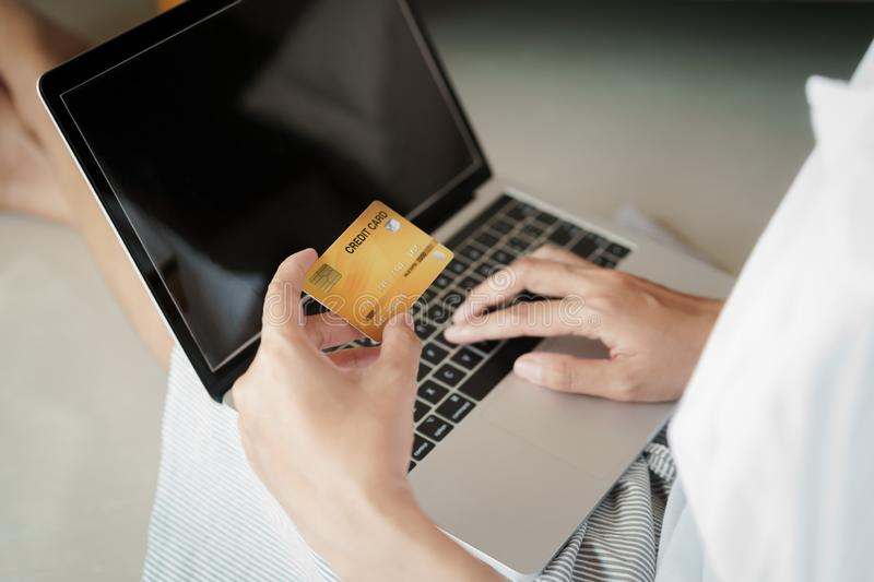 Close up hand of women are buying online with a credit card. woman are using laptop and doing online transactions stock photo