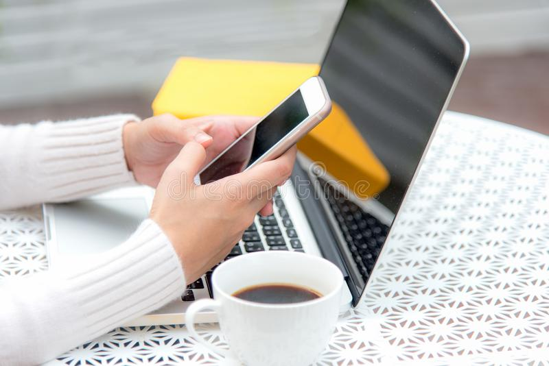 Close up hand women play smart phone for sale online. Work space relaxing chill out work for office and design laptop stock photo