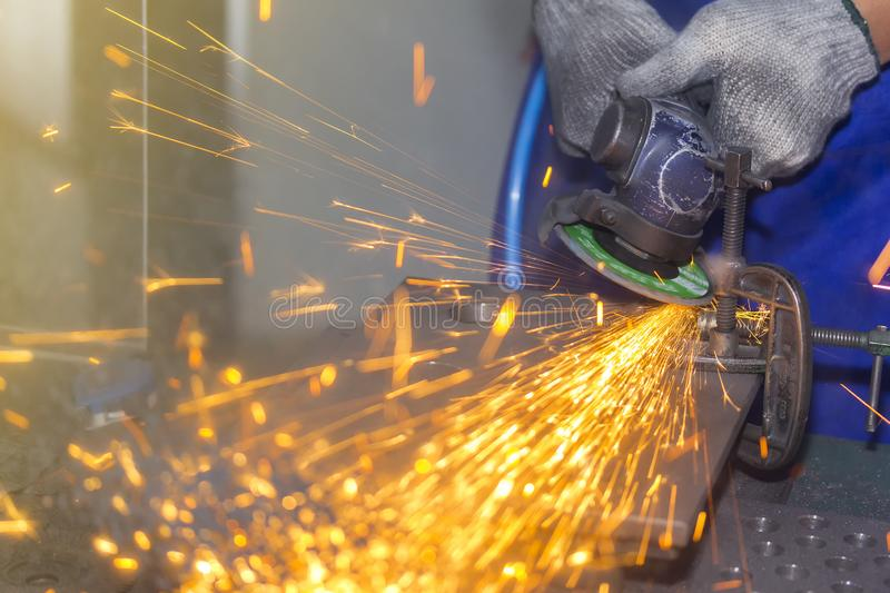 Close up hand worker and electric wheel grinding machine and spark light royalty free stock photography