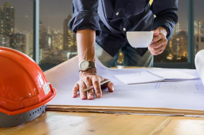 Close up hand of Young Engineer man holding cup of coffee and pe. N and working on his plane project with blue print at site construction work to night. vintage royalty free stock photos