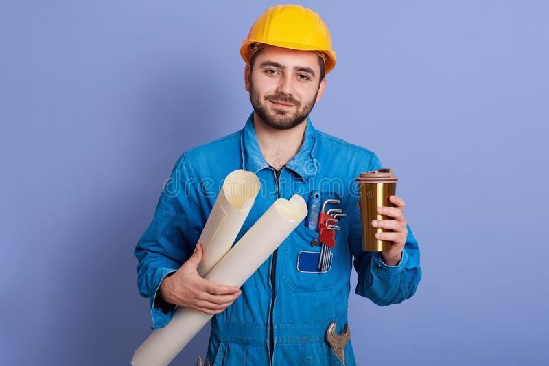Close up hand of young handsome Engineer man holding coffee or tea in thermo mug, working on his plane project with blue print,. Having break, looks at camera stock photos