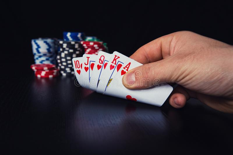 Close up hand of young man poker player checking cautious at his playing cards stock photography