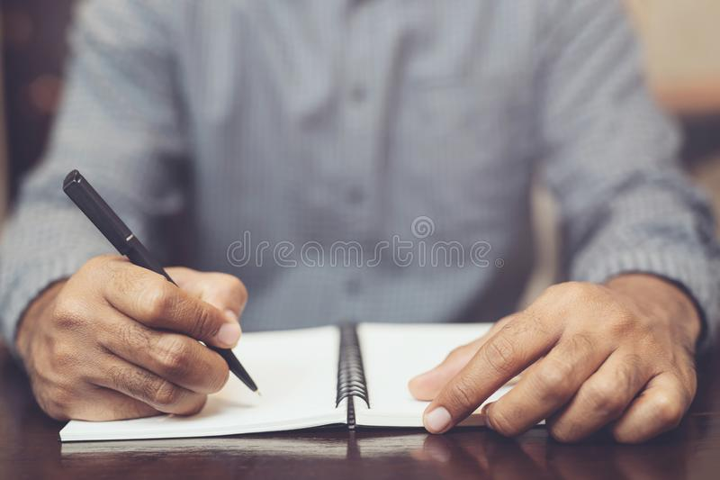 young man hand are sitting using pen writing Record Lecture note pad diary into the book stock photos