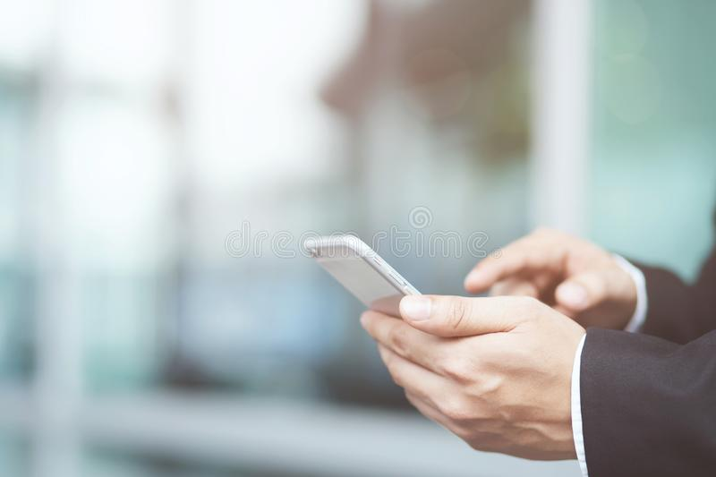 Close up hand young man in watching message on mobile smart phone during break. using cell phones to communicate in the online w royalty free stock photography